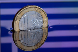 epa04547273 An illustration picture shows a one euro coin in water, which reflects the Greek flag, in Schwerin, Germany, 05 January 2015. The situation in Greece and the monetary policy of the ECB have caused the commom currency euro to drop to its lowest rate since 2006.  EPA/JENS BUETTNER